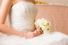 Bridal Bouquet. Bride holds bridal bouquet, pink couch on background Royalty Free Stock Photo