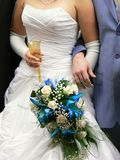 Bridal bouquet. Hands of a bride holding bouquet and a glass of champagne with groom nearby Royalty Free Stock Photography