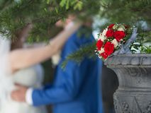 Bridal bouquet against newly wedded couple Royalty Free Stock Images