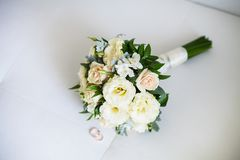 Free Bridal Bouquet And Rings Lie On White Sofa Royalty Free Stock Images - 161435999