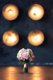 Bridal bouquet on a background of lights. Bridal bouquet on a background of light on the wooden floor in the reflection of light Stock Photography