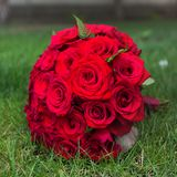 Beautiful bridal bouquet from red roses on grass outdoors Royalty Free Stock Photos