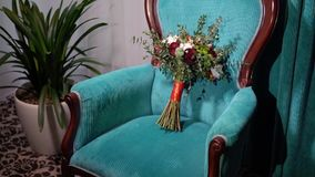 Bridal bouquet on blue chair. In room stock footage