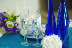 Bridal bouquet of blue iris white tulips glasses and bottles Stock Photo