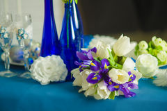 Bridal bouquet of blue iris white tulips glasses and bottles Royalty Free Stock Image