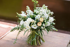 Bridal bouquet. The bride`s . Beautiful of white flowers and greenery, decorated with silk ribbon, lies on vintage Stock Photography
