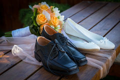 Bridal bouquet and bride's shoes. On desk Royalty Free Stock Image