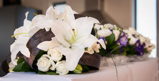 Bridal bouquet. With bridesmaid bouquets in the background. Made of lilies, roses and flax royalty free stock image