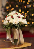 Bridal Bouquet. A Christmas themed bridal bouquet featuring white roses red berries and some greens is pictured, wrapped in ribbon in a vase.  In the background Stock Photography