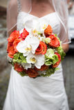 Bridal bouquet. Closeup of bride in white veil and wedding dress holding bouquet of mainly salmon pink roses and white lilies stock photography