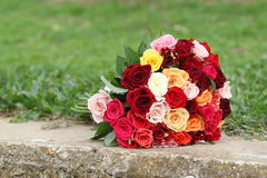 A bridal bouquet. A bridal colorful bouquet, roses Lying on the ground and grass, Colors pink, red, white, Maroon, Orange, yellow, Marriage, wedding Stock Images