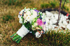 Bridal bouquet of different flowers wrapped lace ribbon on green grass Royalty Free Stock Images