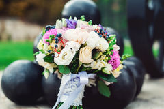 Bridal bouquet of different flowers wrapped lace ribbon near bunch of cannonballs Royalty Free Stock Photos