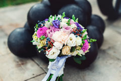 Bridal bouquet of different flowers wrapped lace ribbon near bunch of cannonballs Royalty Free Stock Image