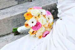 Bridal bouquet and dress. White bridal dress and colorful bouquet of flowers on steps Royalty Free Stock Photo