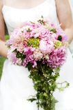 Bridal Bouquet of flowers. A bride is holding her beautiful bouquet of mixed flowers. NOTE: This is a soft focused image, with a fade out from the center of the stock images