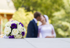 Bridal bouquet. In the foreground and the bride with the groom in the background Royalty Free Stock Photography