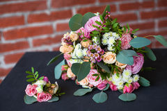 Bridal bouquet of fresh flowers and grooms boutonniere o Royalty Free Stock Photos