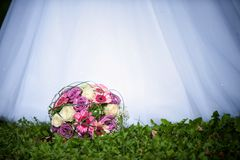 Bridal bouquet. In front of the wedding dress Royalty Free Stock Images