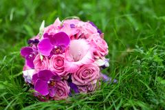 Bridal  bouquet in a grass. Bridal bouquet of pink flowers lying in a green grass Stock Photography