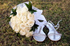 Bridal bouquet on the grass. Near sandals Royalty Free Stock Photography