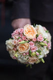 Bridal bouquet in hand of groom Stock Photography