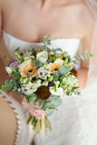 Bridal bouquet in hands. The bride holds a gentle bouquet in hand Royalty Free Stock Images