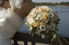Bridal bouquet in her hand the bride. Beautiful wedding roses, the bride against the backdrop of the picturesque Siberian river, a wonderful summer day, the Royalty Free Stock Photography