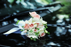 Bridal bouquet on the hood. Of a black car Royalty Free Stock Photos