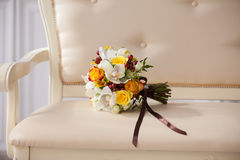Bridal bouquet in an interior. Delicate bouquet of the bride on a beige couch in a classic interior Royalty Free Stock Images