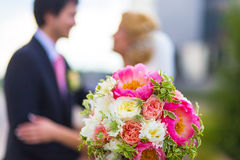 Bridal bouquet on kissing newlyweds. Backgound Stock Photography