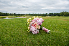 Bridal bouquet lies on a huge green lawn. For golf.  Bouquet of flowers is a different kind: peonies, roses, euston and tied with a pink ribbon with white lace Stock Photography
