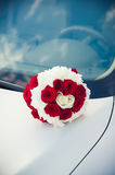 Bridal bouquet lying on the hood of a car stock photo