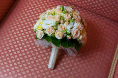 Bridal bouquet lying on a red couch Royalty Free Stock Image