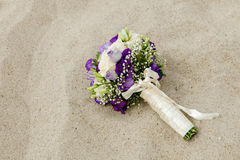 Bridal bouquet lying on the sand Royalty Free Stock Photos
