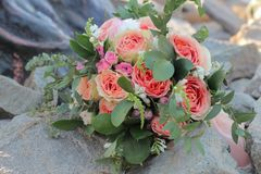 Bridal bouquet lying on the stones. Wedding bouquet of peach roses by David Austin,  single-head pink rose aqua, eucalyptus, ruscu Royalty Free Stock Image