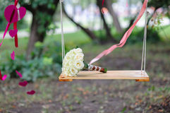 Bridal bouquet lying on the white swing Stock Image