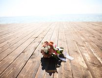 Bridal bouquet. Lying on wooden floor near sea royalty free stock images