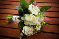 Bridal bouquet lying on a wooden table closeup. Bridal bouquet lying on a wooden table, tinting. Bouquet of white peonies closeup Royalty Free Stock Images