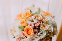 Bridal bouquet made of white, pink and orange roses with two wedding rings on top. Close-up Stock Photos