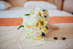 Bridal bouquet with male studs on the bedspread Stock Photos