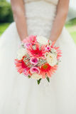 Bridal bouquet of pink flowers. In the hands of the bride's wedding dress on a background Stock Image