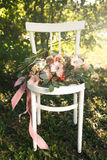 Bridal bouquet of pink flowers and greenery, lies on vintage white wooden chair. Bridal bouquet of pink flowers and greenery with ribbon, lies on vintage white Royalty Free Stock Photos