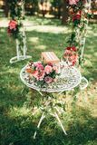 Bridal bouquet with pink and purple flowers. Two glasses and gift box on white round table, wedding arch on background Stock Image