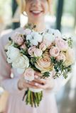 Bridal bouquet from pink roses and white tupils in young bride hands, focus of flowers.  Spring freshness of tulips and roses in o. Ne delicate bouquet. Close up Stock Photos