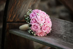 Bridal bouquet of pink roses on wooden bench Royalty Free Stock Photography