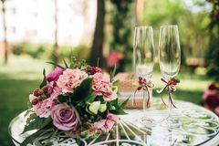 Bridal bouquet with purple penies and roses flowers. Bridal bouquet with purple flowers and two glasses on white round table Royalty Free Stock Photography