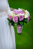 Bridal bouquet of purple roses in bride's hands Stock Image