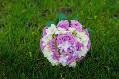 Bridal bouquet of purple roses on the grass Royalty Free Stock Photos