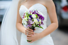 Bridal bouquet of purple and white flowers in hands of the bride Royalty Free Stock Photos